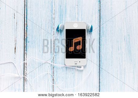 smartphone with earphone and note symbol on screen