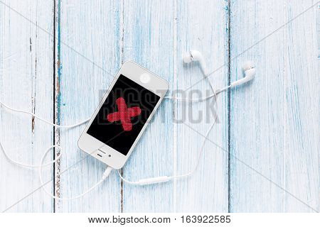 smartphone with earphone and cross symbol on screen