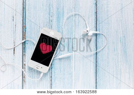 smartphone with earphone and heart symbol on screen