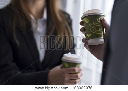 Detail of a young business people on a coffee break by the office window