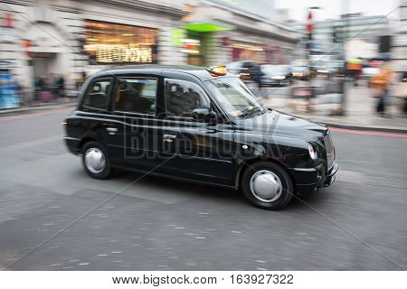 London, UK - 19 December 2016: Black cab taxi in motion on the London's street
