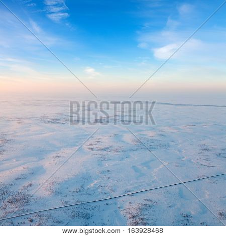 Trucks moving on highway in winter tundra, Aerial view
