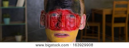 Close shot of a man's face painted in German flag colours