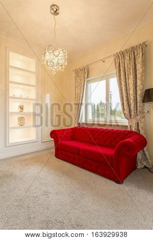 Bright room with luxurious red couch and elegant doors