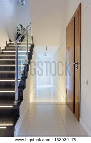 Stylish villa corridor with modern design and dark stairs