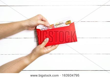 Red Envelope or red packet with money in side for Chinese New Year Gifts held in hand on the white wooden plank background Traditional Celebration Chinese New Year.