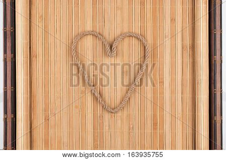 Symbolic heart made of rope lying on a furled bamboo mat as background conceptual image