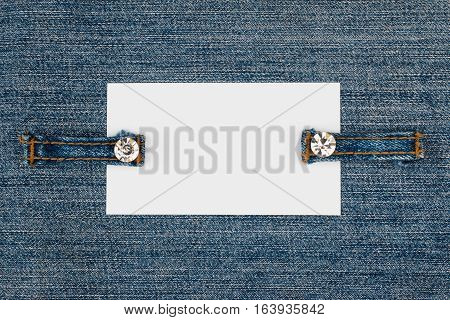 Business card with two straps jeans lies on the light denim with space for your text