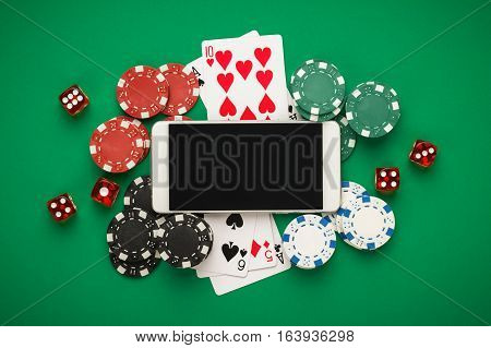 online casino concept. casino cards, dice chips and smartphone with copy space. online casino games on the green table. casino table view from above. banner template layout  mockup for online casino and gambling.