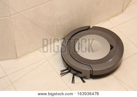 Small robotic vacuum cleaner sucks up tiles in the bathroom