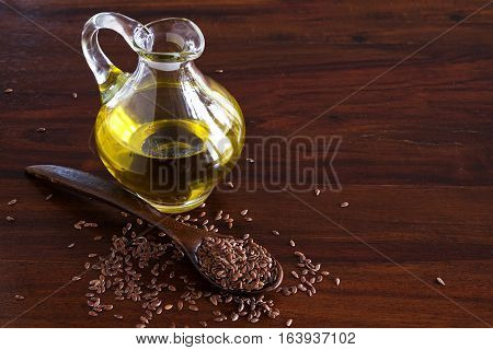 flax seeds on a spoon and linseed oil in a glass jug on a dark wooden table copy space