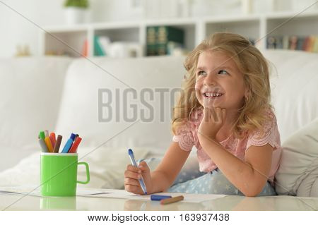 little girl drawing on white paper with blue crayon