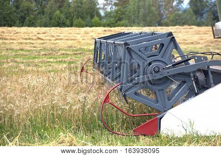 Grain harvester agricultural rotary combine works on a field on summer day. Side view closeup