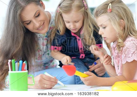 mother with two little daughters, drawing together
