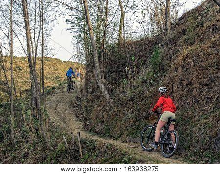 Mountain biking in Nepal. Young woman with group of mountain bikers. Group of mountain bikers biking near Kathmandu Nepal.