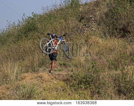 Mountain biking in Nepal. Young woman nountain biker carrying her bike. Biking near Kathmandu Nepal.