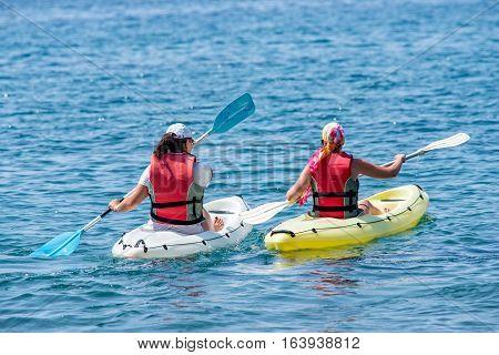 Two young ladies kayaking white and yellow kayaks