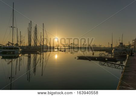 panoramic view sunrise at the Valencia harbor, the sun rises between docked sailboats and cargo port cranes, water reflection