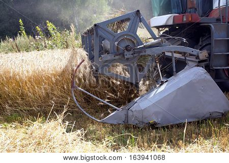 Grain harvester agricultural rotary combine in a field on summer day. Side view closeup