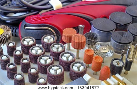 Mini drill machine with set of different grinding and cutting accessories closeup