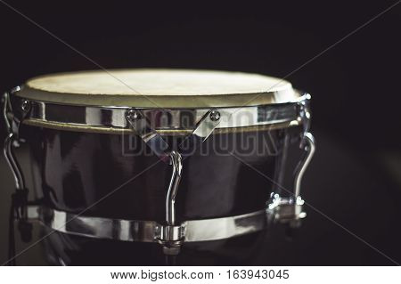 Goblet drum or darbuka percussion musical instrument on dark background. Toned image
