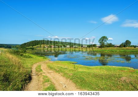 Dirt road disappearing into the river. The village Sulyom on a summer day. Russia