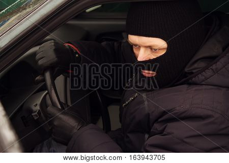criminal in a mask hijacks at the wheel auto