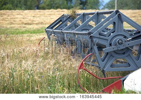 Grain harvester agricultural rotary combine in a field on summer day. Photo closeup