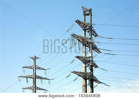 Two high-voltage power line grey metal props with many wires vertical view over clear cloudless blue sky bottom-up view