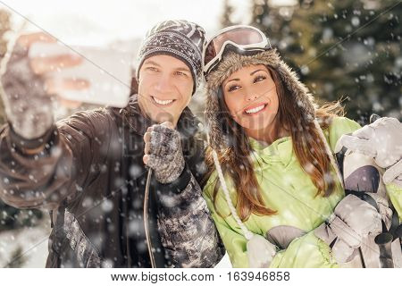 Portrait of a beautiful smiling couple taking selfie on winter vacations.