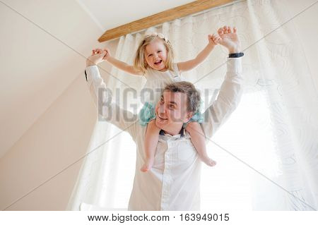 The young man gaily spends time with the little daughter. Charming baby sits on shoulders at the father and cheerfully laughs.