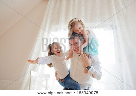 The young man cheerfully spends time with the little daughters. Younger girl sits at the father on shoulders another trying to climb the dad. Children and father delighted with a play.