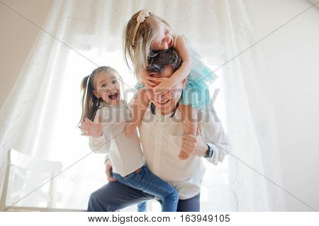 Young father cheerfully spends time with the little daughters. Younger girl sits at the father on shoulders and closes his eyes with her hands. Another has settled down on a father's leg.