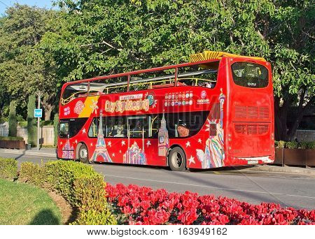 PALMA DE MALLORCA SPAIN - DECEMBER 11 2016: Red tourist sightseeing bus and red flowers in the city on December 11 2016 in Palma de Mallorca Spain.