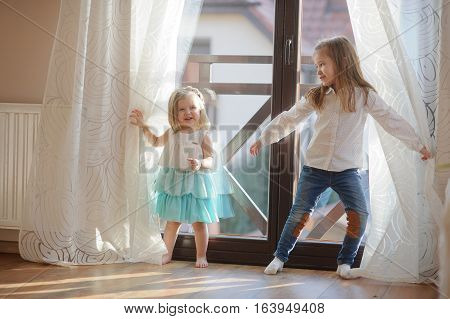 Two little sisters play in the room. Girls hide behind curtains and then joyfully jump out because of curtains.