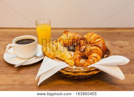 cup of coffee with croissant in a basket orange juice Stock image