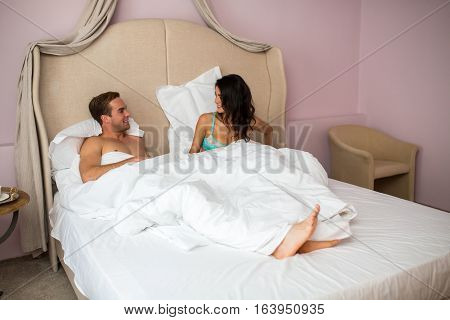 Young caucasian couple in bed. People under white blanket. Spend weekend with beloved.