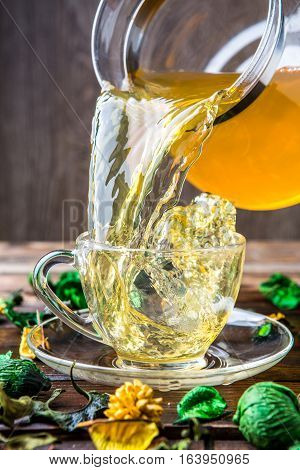 Slop green tea from mug on brown wooden background