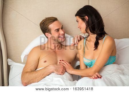Couple in white bed. Man smiling to a woman. Romance and mood.