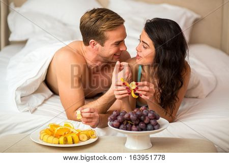 Couple eating fruits in bedroom. Grapes and sliced bananas. Better eat vitamins, darling.