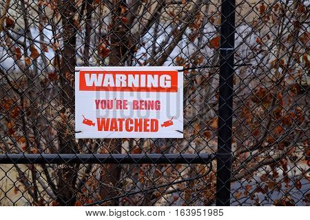 A warning sign for video cameras on a fence in a secure area.