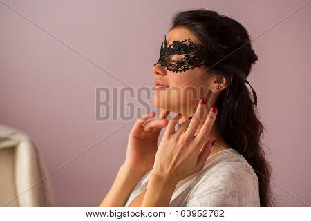 Lady wearing lace mask. Woman with closed eyes. Look gorgeous and charming.