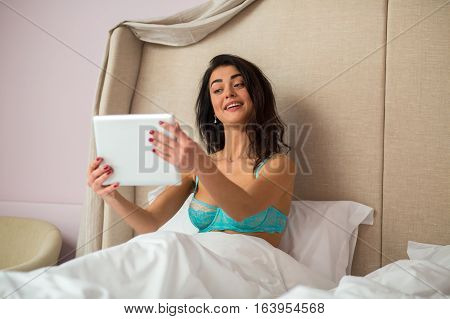 Lady holding tablet in bed. Girl with a gadget. Stable video connection.