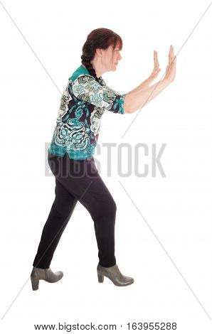 A pretty middle age women standing in profile with her hands up and pushing something away isolated for white background.