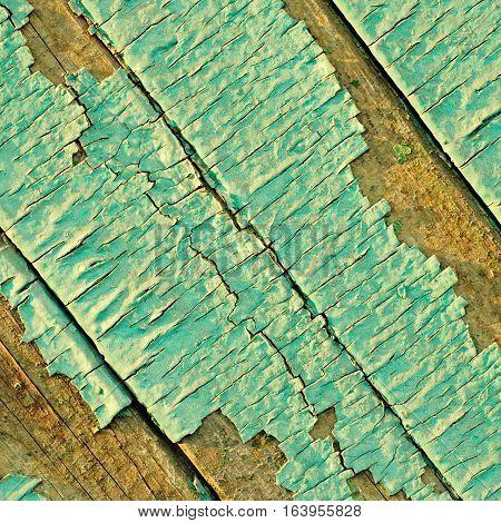 Peeling paint with many cracks on diagonal wood background. Square toned image