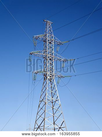 High-voltage power line grey metal prop with many wires vertical view over clear cloudless blue sky vertical view