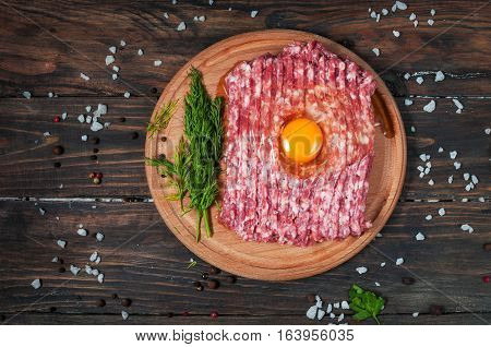 Homemade raw minced meat with egg and herbs closeup top view.
