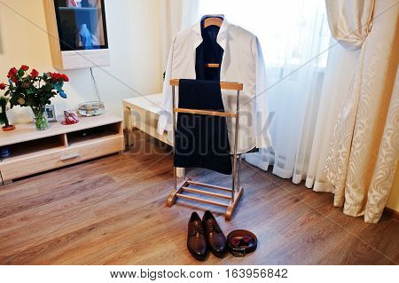 Shirt With Trousers On A Hanger With Shoes And Men's Accessories. Set Of Groom Clothes On Wedding Da