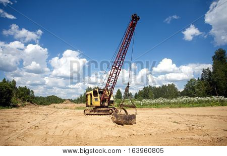 Yellow excavator with big heavy bucket standing on sand on background of forest and clear blue sky on a summer day