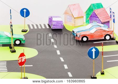 Playing set with road sings, crossings and colored paper cars on parking